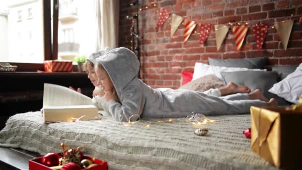 Kinder sind gekleidet in warmen Xmas Pyjama Buch ein Interesse auf dem Bett sitzt, Hintergrund schmücken Weihnachten und Geschenke