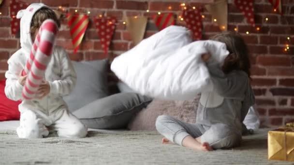 Spielerische Geschwister im warmen Xmas Pyjama kämpfen mit Kissen zu Hause, Bruder und Schwester zusammen spielen am Weihnachtsmorgen, Frohe Weihnachten