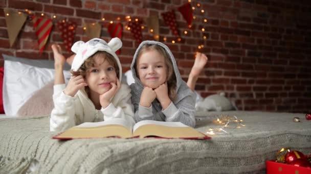 Glücklich niedliche kleine Kinder gekleidet sind in warmen Xmas Pyjamas lacht und schaut in die Kamera Lächeln Kinder Buch liest bei der Weihnachtsmorgen