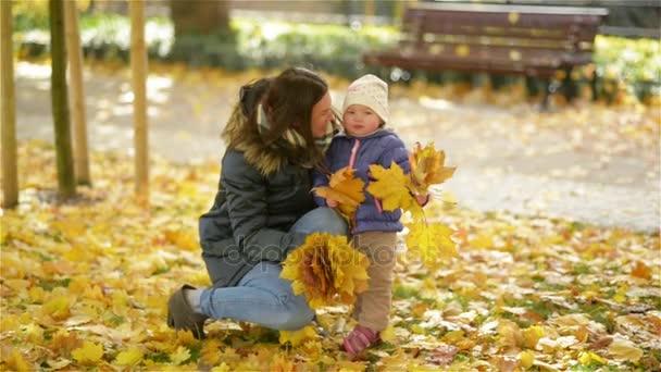 Šťastná rodina, matka a dítě, malá dcera hraje a drží listy, směje se mazlení na podzimní procházka v přírodě venku