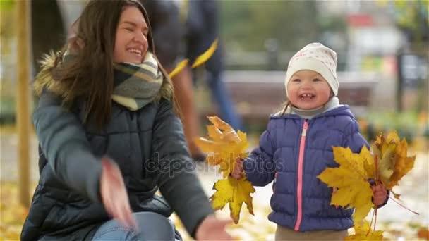 Happy mladá matka a její malá dcera baví v podzimní Park, Maminka a dívka házel listí a rajský