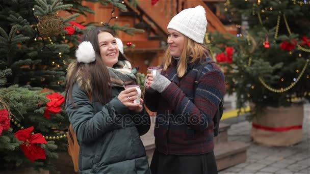 Zwei schönen Freundinnen reden und Lachen auf dem Weihnachtsmarkt ...