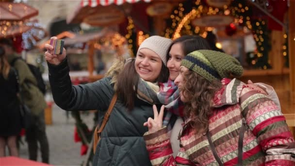 Three Girlfriends Taking a Selfie with Smart Phone on the Christmas Market. Happy Women Having Fun Outdoors on the Xmas Fair. Merry Christmas and Happy New Year