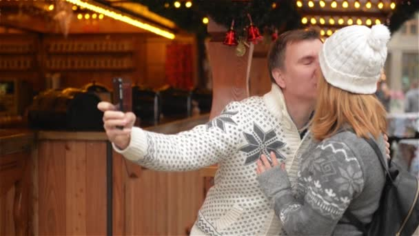 Technology and People concept. Happy Couple of Tourists in Warm Clothes Taking Selfie with Smartphone on the Christmas Market. Young Family Laughing and Kissing on the Xmas Fair
