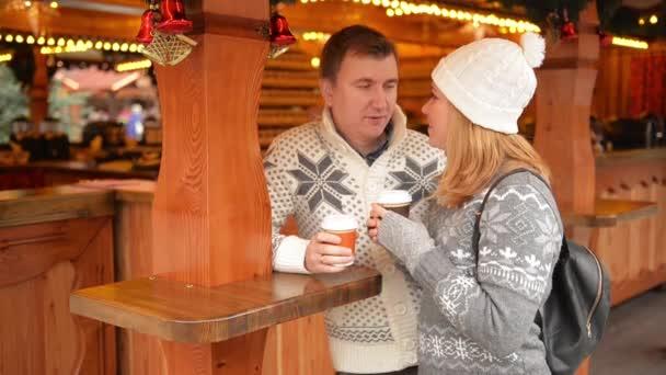 Glückliches Paar in warme Kleidung, trinken Kaffee und reden über ...