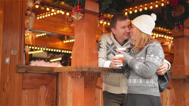 Ein glückliches junges Paar, das sich auf dem Weihnachtsmarkt amüsiert und küsst, eine schöne Familie, die zusammen chillt und auf dem Weihnachtsmarkt Kaffee trinkt. Frohe Weihnachten und ein gutes neues Jahr