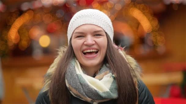Detail portrét krásné usměvavé mladé ženy nosit teplé oblečení. Dívka se smíchem a při pohledu na fotoaparát, vánoční jarmark na pozadí. Veselé Vánoce a šťastný nový rok