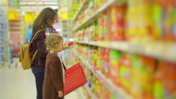 Mladá žena a roztomilý dívka stojící poblíž police zboží v supermarketu. Máma s dítě nakupování společně v části šťávy v obchodě