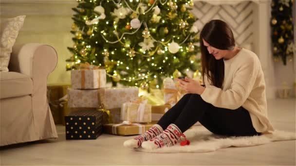 Krásná emotivní bruneta SMS na miniaplikaci a usmíval se další velké vánoční strom a boxy s dárky. Mladá žena s dlouhými tmavými vlasy, sedí na podlaze pomocí telefonu