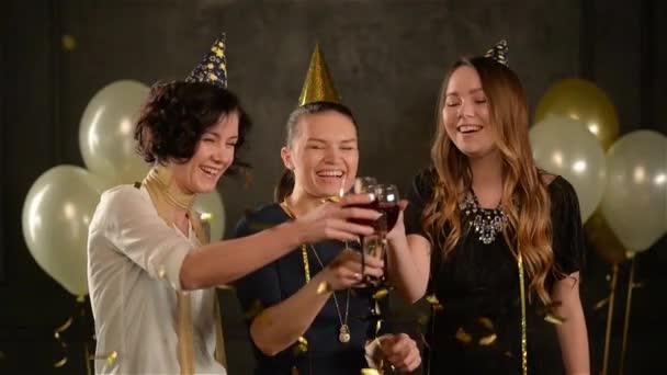 Tři ženy cinkání skleniček a se smíchem si oslavu narozenin mezi zlaté konfety. Mladé dámy bavit během oslav čepičkách a pít alkohol