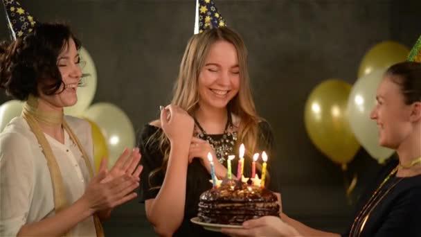 Két Női sapkák énekelni boldog születésnapot a dalt, hogy a barátja, és így a csokoládé torta. Csodálatos hölgy fúj gyertyát ünnep alatt. Arany és fehér levegő léggömbök fekete háttér.
