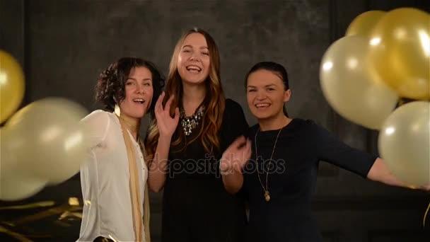 Drei Mädchen verstecken sich hinter den goldweißen Luftballons, erscheinen dann plötzlich und lächeln breit in die Kamera. aufgeregte Frauen haben Spaß im Studio auf schwarzem Hintergrund.