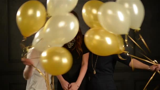 Excited Surprised Women Hiding among Balloons Having Fun during a Party. Closeup Portrait of Three Smiling Girls in the Studio on Black Background.