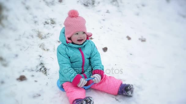 3c0227d86 Toddler Girl Wearing Warm Snow Suit and Pink Knitted Hat is Sitting ...