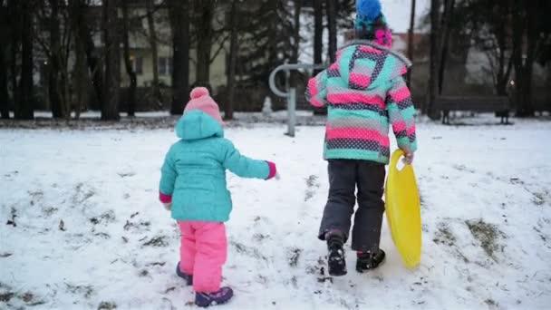 Zwei kleine Schwestern in bunten Kleidern genießen das verschneite Wetter und Schlitten und versuchen, den Hügel hinauf zu klettern. lustige Mädchen haben Spaß im Freien.