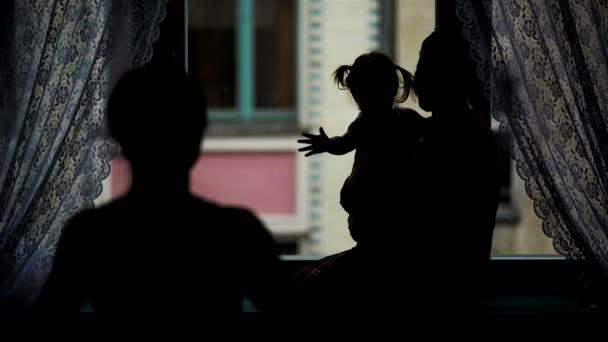Zadní pohled šťastné rodiny objímání u okna. Silueta matky, otce a jejich malou dceru s dvěma ohony všeobjímající a usmívá se doma