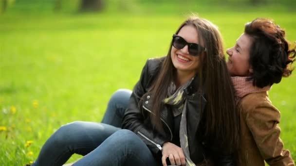 Gondtalan a két lány birtoklás móka a zöld fű hétvégén a parkban. Mosolygós boldog fiatal nők tölti együtt az időt a szabadban