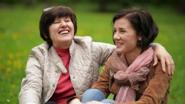Two Smiling Brunette Women are Talking to Each Other Sitting on the Blanket During the Picnic in the Park. Portrait of Adult Daughter with Short Curly Hair and Her Mother.