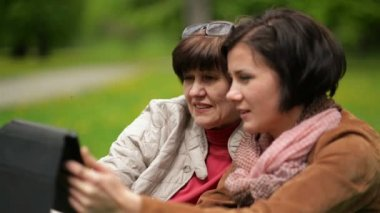 Closeup Portrait of Pretty Mother and Mature Daughter Using Tablet Together Outdoors. Two Brunette Women is Looking on Gadget Screen in the Park.
