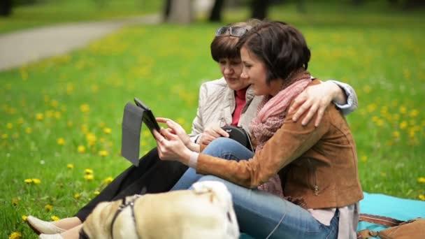 Šťastná rodina s malým psem během jarní piknik v parku. Dospělá dcera s její matkou je používání Tablet venku