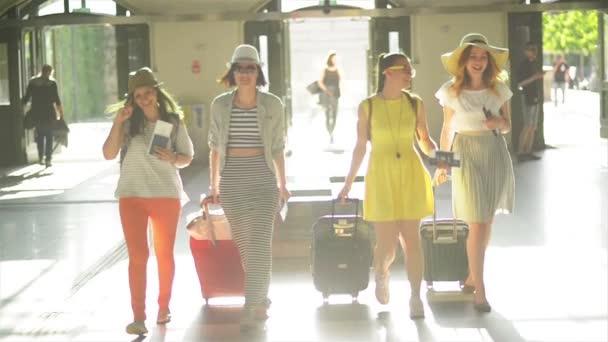 Nástupu na letišti budou čtyři docela ženy v jasný letní oblečení s dokumenty, jízdenky a velké kufry v rukou. Sluneční světlo na pozadí