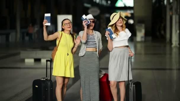 Tři usmívající se dámy nosí světlé letní oblečení jsou Happy Together mají dovolenou. Celé její výšce portrét kamarádky na letišti s dokumenty a lístky v rukou.