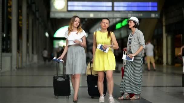 Tři úžasné dívky s dokumenty v rukou a vstupenky jsou v přehledu na letišti a bude na palubu jejich letadla