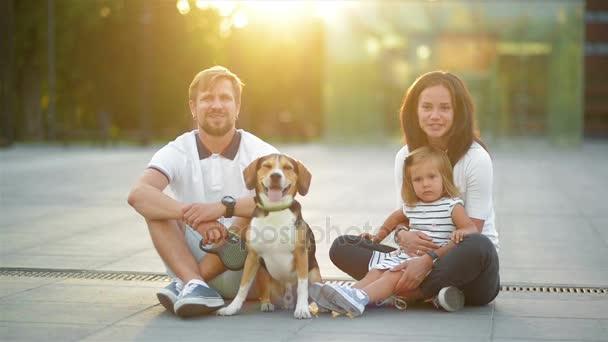Portrét venku mladá rodina s malou dcerou a jejich pes Beagle v městě během letní západ slunce.