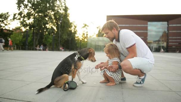 Hezký vousatý otec tráví čas se svou dcerou při západu slunce ve městě. Pes Beagle dává tlapku na holčičku.