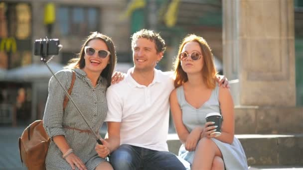 Front View Of Three Happy Friends Taking Selfie Using Smartphone Outdoors On The City Square During