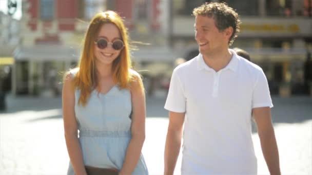 Šťastné setkání tří přátelé objímání na ulici během teplých letních dnů. Dvě dívky nosí sluneční brýle a krátké šaty a pohledný kluk bílou košili a džínách, s úsměvem a všeobjímající venku