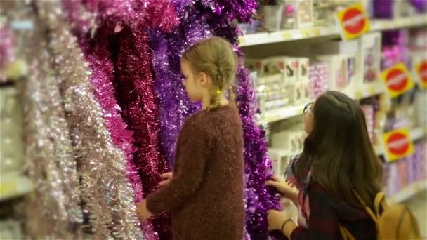 People Buying Xmas Toys and Tinsel at Christmas Market , Mother and Child Choosing Festive Decoration in the Shop Mall. Merry Christmas and Happy New Year
