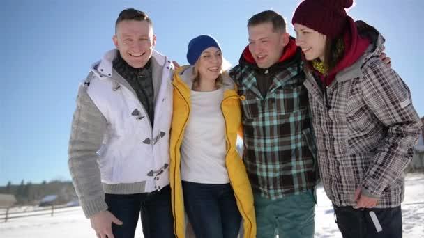 Ritratto del primo piano di due coppie felici durante le loro vacanze invernali in montagna. Sono quattro amici che abbraccia laltro sul fondo del cielo blu.