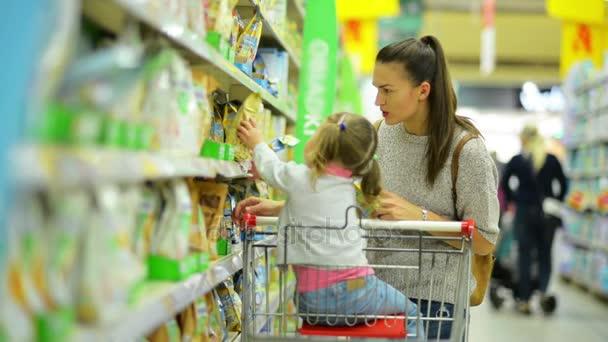 Uvnitř portrét mladé atraktivní Maminka a malé dítě, nákup potravin v supermarketu. Boční pohled na šťastnou rodinu vybrali produkty s nákupní košík