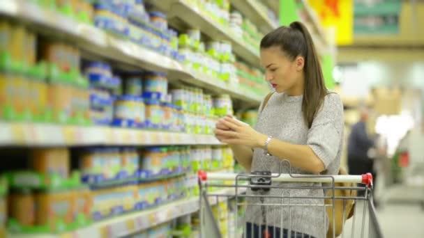 Úžasná brunetka matka s nákupní košík nákup zdravé dětské výživy v hypermarketu, stojící poblíž police s zboží