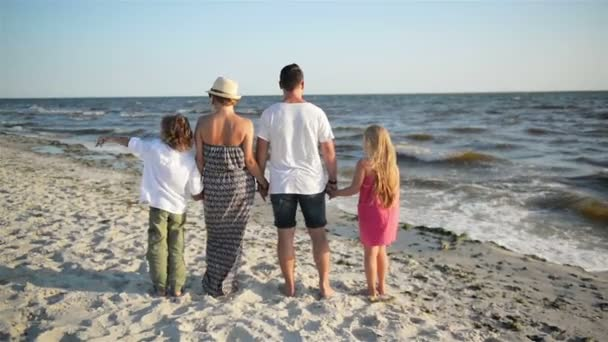 Back View of Happy Family Looking on the Sea During Summer Vacation. Mother, Father, Son and Daughter Holding Hands on the Beach.