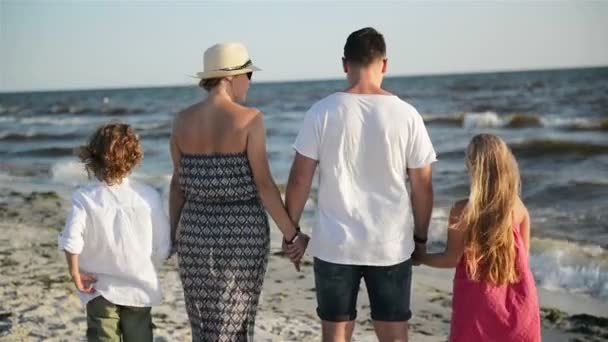 Outdoors Portrait of Mother, Father, Son and Daughter Holding Hands on the Beach During Sunny Windy Day near the Sea.