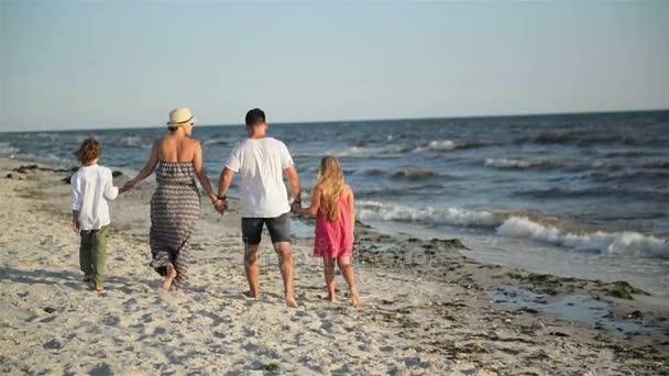 Zadní pohled na čtyřčlenná rodina chůzi na pláži během letní dovolené u moře.