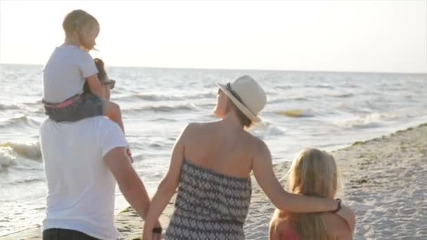 Back View of Two Little Sisters and Happy Mother and Father Walking Together around the Beach Holding Hands During Summer Vacation on the Seaside.