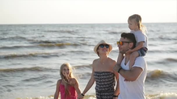Portrait of Happy Family Walking Together around the Beach During Summer Vacation on the Seaside. Strong Father Holding One of the Daughters on His Shoulders.