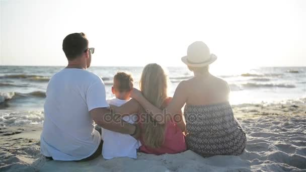 Back View of Mother, Father, Son and Daughter Hugging on the Beach near the Sea.