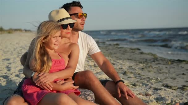 Happy Family with a Daughter on Vacation Sitting at the Beach. Smiling Parents in Sunglasses with a Kid Enjoying Sunset.