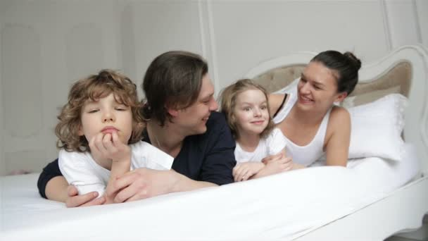 Portrait of Young Couple Spending Weekend with Their Children at Home. Little Boy and Girl with Two Adults are Relaxing Together on White Parents Bed.