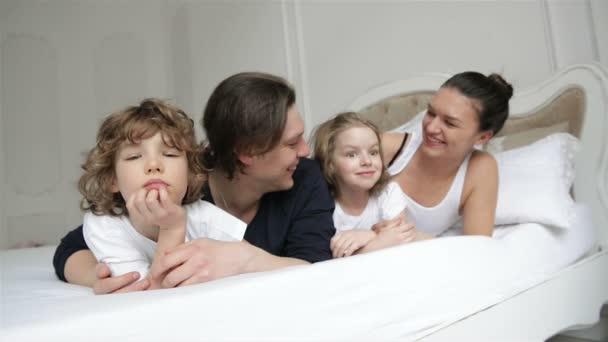 Portrét mladého páru víkend s dětmi doma. Malý chlapec a dívka se dvěma dospělými jsou relaxační společně na bílém rodiče posteli