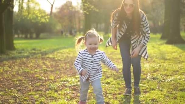 Legrační malá holčička je běh pryč od její maminky. Matka a dcera v pruhovaném oblečení jsou hrát společně užívat teplého jarního počasí v parku