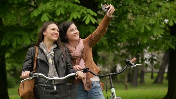 Attractive Female Bicyclists are Photographing Themselves Using Smartphone Outdoors in the Park During Spring Time. Two Girls with Charming Smiles are Taking Photo by Mobile Phone Outside.