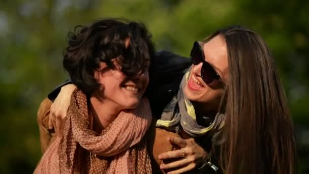 Amazing Woman with Short Curly Hair is Carrying Her Female Friend in Sunglasses on the Shoulders.Two Attractive Brunettes is Having Fun Outside Enjoying Sunlight in the City Park.
