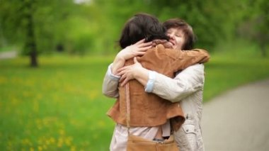 Amazing Brunette is Hugging Her Mother with Love and Tenderness in the Park. Portrait of Adult Daughter and Her Mom Outdoors.