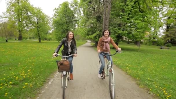 Two Female Friends are Riding on Bicycles in the Park During the Spring. Front View, Camera in Motion.