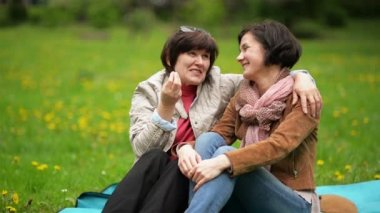 Brunette with Short Hair is Enjoying Communication with Her Mother Sitting on the Blanket During the Picnic in the Park. Adult Daughter with Mom Spending Time Together Ourdoors.